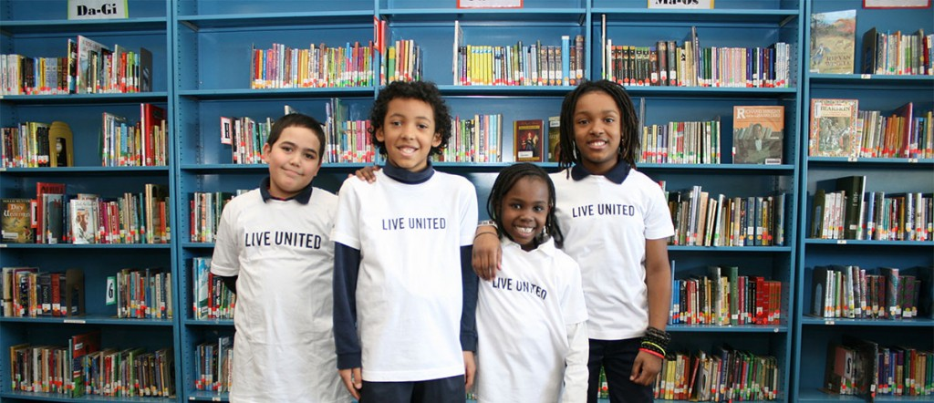 Group of happy children, all wearing 'Live United' shirts, pose together in a classroom.