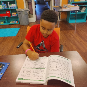 Young boy writing in a study book at a recent Summer Care program.
