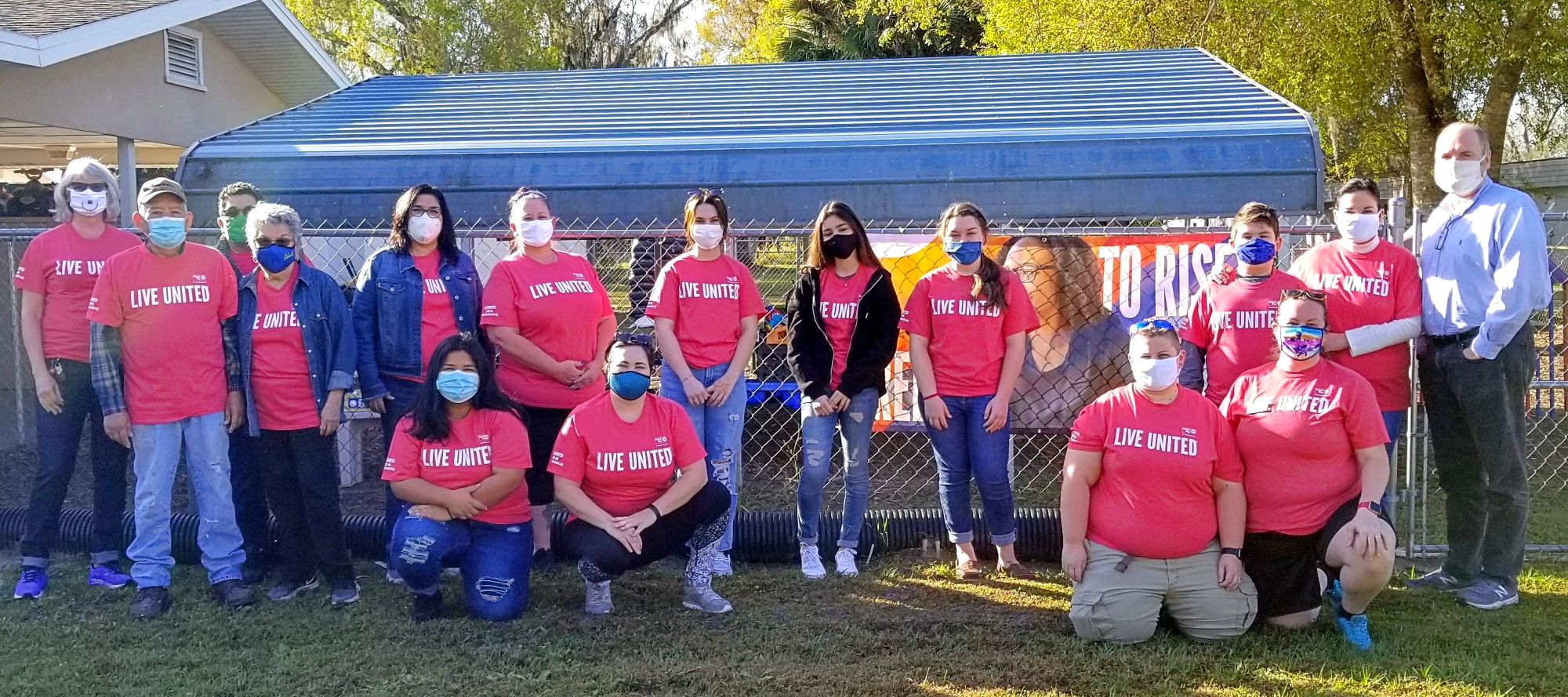 """Group of adult volunteers pose for photograph. All wear red shirts bearing the message: """"LIVE UNITED""""."""