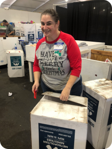 Woman smiling and posting for a photo while opening a box with a box cutter
