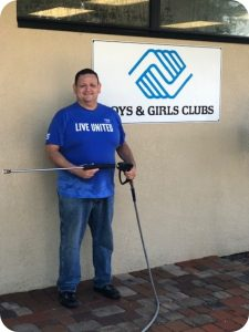 """Man in blue """"Live United"""" shirt holding a pressure washer in front of a Boys & Girls Clubs sign"""