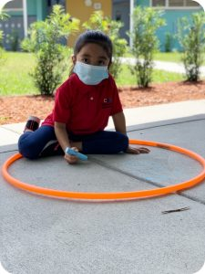 Child with face covering sitting inside a hula hoop while drawing with chalk on sidewalk